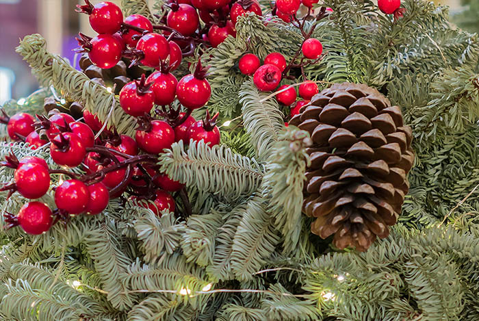 closeup of holiday decorated porch pot with berries, lights and pinecones