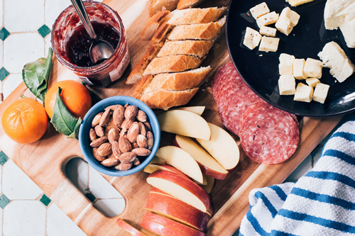 Chacuterie Board with apples, bread slices, nuts, cheese, salami